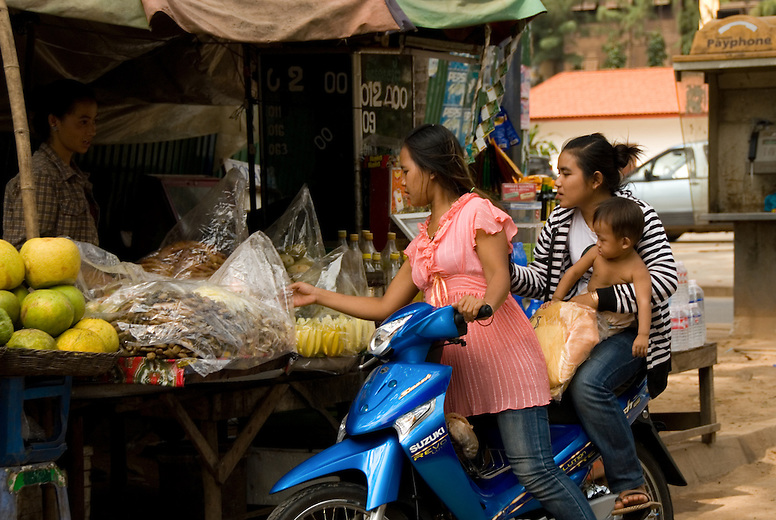 Kids in a small village around 30 km from Siem Reap visit the market on their motor bikes. Life in the small villages is very different to life in the city of Siem Reap despite it's proximity. The average family in Cambodia lives on less than a dollar US per day -- and even lower in rural areas such as this one