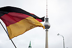 A German flag being waved aloft with the television tower in the background during a demonstration by the Alternative für Deutschland (AfD) political party through the centre of Berlin. Around 5000 supporters of the AfD took part in the march and rally calling on German Chancellor Angela Merkel to halt the influx of refugees into the country. Around one million refugees from the Middle East and north Africa arrived in Germany during 2015, 50,000 of whom came to Berlin.