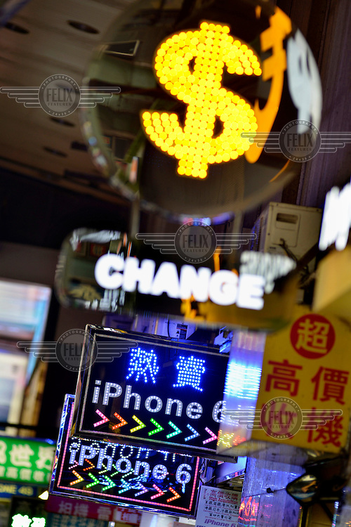 Signage outside an electronics emporium in Mongkok District offering money exchange and deals on the latest iPhone models.