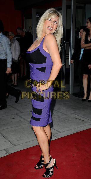 "SAMANTHA FOX .At the ""City Rats"" East End Film Festival VIP Screening, Genesis Cinema, Mile End Road, London, England, UK, .April 24th 2009..full length black and purple dress hands on hips booties sandals shoes looking back over shoulder .CAP/CAN.©Can Nguyen/Capital Pictures"