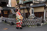 "Japan; Kyoto. Kikugawa, a Tayu or Oiran. Once known as a courtesans, they are highly educated in tea cermony, flower arranging, playing music, calligraphy, are well read and good conversationists. Her black teeth are a sign of beauty. Therare about 5 tayu today, compared to about 300 geisha. ""A tayu is my ideal woman image, I chose to be one. I was also concerned that this culture would disappear."" Tayu walking down the street. Model released."