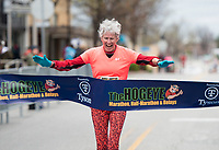 NWA Democrat-Gazette/CHARLIE KAIJO Kay Evans of Chocowinity, N.C. crosses the finish line to place first during the The 42nd annual Hogeye Marathon, Saturday, April 14, 2018 in Downtown Springdale.