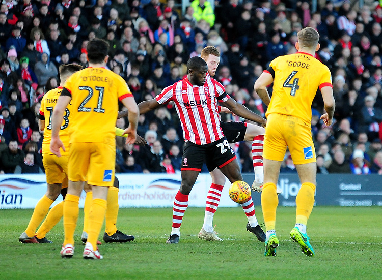 Lincoln City's John Akinde shields the ball from under pressure from Northampton Town's Jordan Turnbull, left, John-Joe O'Toole, centre, and Charlie Goode<br /> <br /> Photographer Andrew Vaughan/CameraSport<br /> <br /> The EFL Sky Bet League Two - Lincoln City v Northampton Town - Saturday 9th February 2019 - Sincil Bank - Lincoln<br /> <br /> World Copyright &copy; 2019 CameraSport. All rights reserved. 43 Linden Ave. Countesthorpe. Leicester. England. LE8 5PG - Tel: +44 (0) 116 277 4147 - admin@camerasport.com - www.camerasport.com