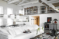 A vast sofa upholstered in crisp white loose covers and designed by Paola Navone for Linteloo divides the living area