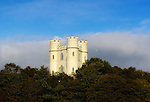 """Haldon Belvedere, Exeter, Devon. A small aircraft flies past Haldon Belvedere in Devon, England. Built in 1788 by celebrated English cleric and politician Sir Robert Palk, the striking triangular structure of Haldon Belvedere, whose three points are marked by identical turret-topped towers, was visited by King George III, albeit late in his reign when he was suffering from an incurable mental illness. The construction of a local carriageway, simply called """"King's Road,"""" predates that visit, indicating that Palk probably had such a brush with royalty in mind. The building is today used as accommodation and wedding venue."""