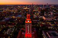 Aerial view of the University of Texas Tower lit with Number 1 bright Orange Tower over looking the Texas Capitol and ever growing downtown Austin cityscape.