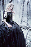 Young woman with blonde plaited hair in black regency dress standing alone in woodland