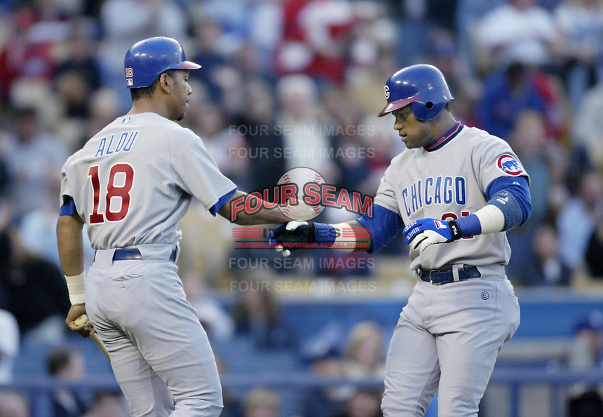 Moises Alou of the Chicago Cubs welcomes teammate Sammy Sosa at home plate during a 2002 MLB season game against the Los Angeles Dodgers at Dodger Stadium, in Los Angeles, California. (Larry Goren/Four Seam Images)