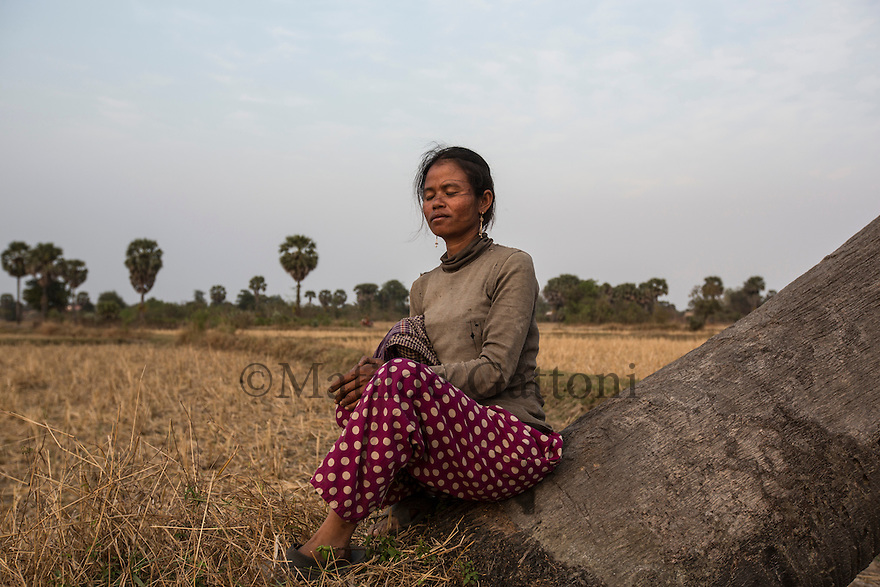 """Cambodia - Kampong Speu Province - Louv Veoun, 39, sits in the rice fields that surround her house and cannot but think of the land she has lost. """"I don't want money, I want my old land back. It is the land of my ancestors"""". Louv Veoun, 39 and mother of 8, was living in a small cottage on her rice field in Kork until March 2010, when she was dispossesed of her two hectares of land and compensated with 25 USD. She was forced to abandon her house and settle in a piece of land belonging to some of her relatives, close to the plantation. Today, she lives in utter poverty together with her family."""