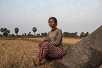 "Cambodia - Kampong Speu Province - Louv Veoun, 39, sits in the rice fields that surround her house and cannot but think of the land she has lost. ""I don't want money, I want my old land back. It is the land of my ancestors"". Louv Veoun, 39 and mother of 8, was living in a small cottage on her rice field in Kork until March 2010, when she was dispossesed of her two hectares of land and compensated with 25 USD. She was forced to abandon her house and settle in a piece of land belonging to some of her relatives, close to the plantation. Today, she lives in utter poverty together with her family."