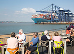 People at Landguard cafe tables with container ship in background, Port of Felixstowe, Suffolk, England, UK