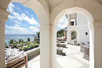 A view through an archway to an outside terrace of a villa giving a view of the sea beyond.