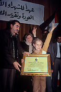 March 1982, Lebanon, Martyrs' Day, a little girl holding her father's death certificate who was killed during an israelian airstrike. Politician leader Nayef Hawaitmeh is giving her the certificate.