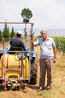 Gezim Coku, agronomist and vineyard manager. In the vineyard with a vineyard tractor and vineyard worker. Spraying tractor. Kantina Miqesia or Medaur winery, Koplik. Albania, Balkan, Europe.