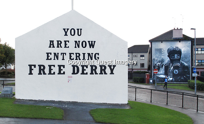 &quot;Free Derry Corner&quot; monument and a mural, on right, &quot;Petrol Bomber&quot; showing a young boy with a gas mask and petrol bomb depicting the Battle of the Bogside, as part of a series of murals called &quot;The People's Gallery&quot; in the Bogside, a neighborhood outside the city walls of Derry, Northern Ireland. The area has been a focus point for many of the events of &quot;The Troubles&quot;.<br />