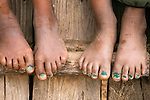 Children's feet sitting on a ladder, Paro Valley, Bhutan
