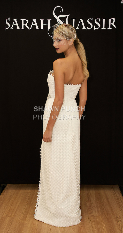 """Model poses in """"Rhea"""" - a strapless guipure lace gown with crystal beaded applique and front slit, from the Sarah Jassir Fall 2013: From Concept To Creation collection, for her Angelique Bridal store opening at 6 East 45 Street, during New York Bridal Fashion Week, October 15, 2012"""