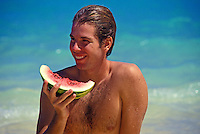 Teenage boy eating watermelon at the beach.