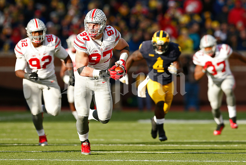 Ohio State Buckeyes defensive lineman Joey Bosa (97) returns an interception of Michigan Wolverines quarterback Wilton Speight (3) during the fourth quarter of the NCAA football game at Michigan Stadium in Ann Arbor on Nov. 28, 2015. Ohio State won 42-13. (Adam Cairns / The Columbus Dispatch)