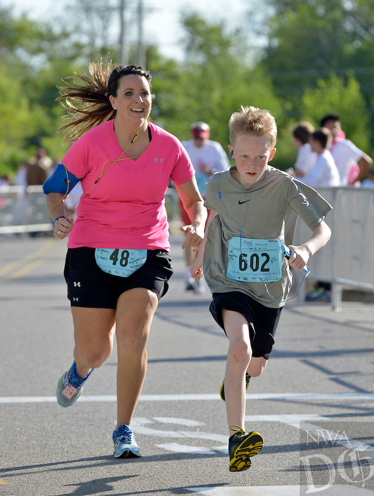 NWA Democrat-Gazette/BEN GOFF -- 04/25/15 Michelle Carter of Centerton and Nick Carter of Bentonville, in the 14 and under age group, finish the competitive 5K run during the Komen Ozark Race for the Cure at Pinnacle Hills Promenade on Saturday Apr. 25, 2015.