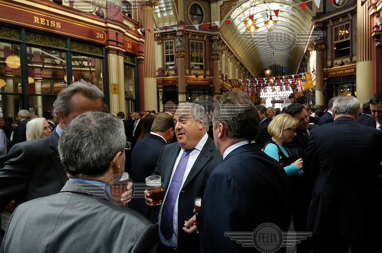 City businessmen at lunchtime, drinking pints of beer standing in Leadenhall Market outside the Lamb Tavern, a popular City drinking spot in London.