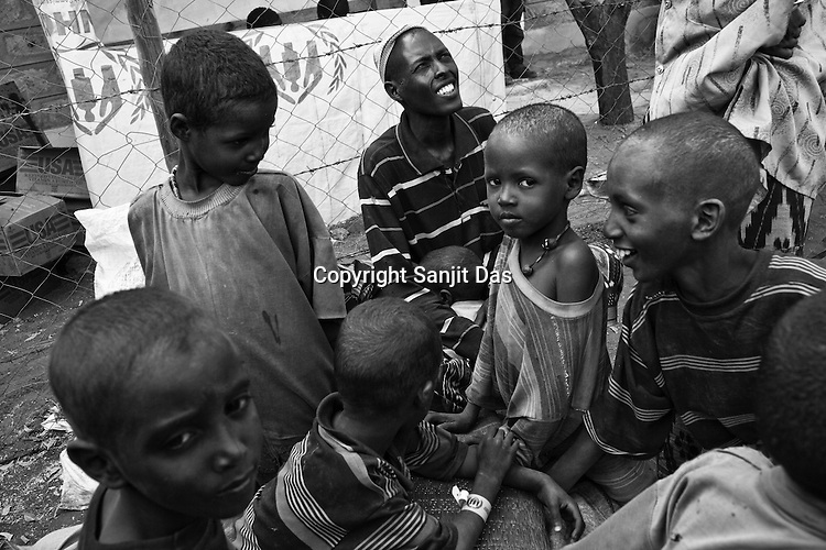 35 year old Mohamed Adan Ibrahim is seen with his children outside a food distribution point in the IFO Camp of the Dadaab refugee camp in northeastern Kenya. Hundreds of thousands of refugees are fleeing lands in Somalia due to severe drought and arriving in what has become the world's largest refugee camp. Photo: Sanjit Das/Panos