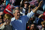 President George W. Bush and his wife Laura wave to those on hand during an outdoor campaign event held on property owned by International Speedway Corp., in Daytona Beach, Saturday, Oct. 16, 2004.(Brian Myrick)