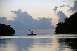 a lone female kayaker is sillouetted against the early evening sky, surrounded by monotone cloud formations, mangrove islands and the waters of Florida Bay in the confines of Everglades National Park