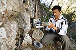 Arabian Leopard (Panthera pardus nimr) researcher Waleed Al'Rail checking camera trap, Hawf Protected Area, Yemen