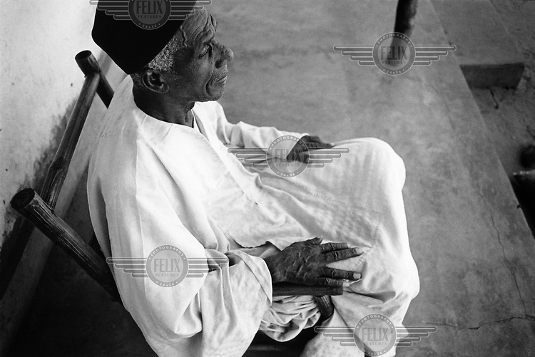 A village elder sits on his veranda.