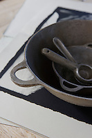 Close up of a cast iron casserole and kitchen utensils
