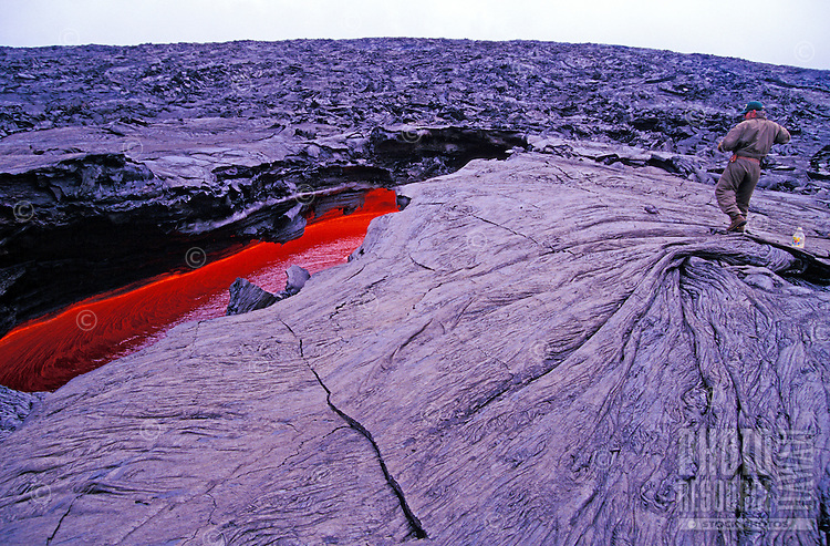 USGS geologists take and record lava samples at Hawaii Volcanoes National Park. Photo shows a red pool of lava in a crevice on hardened lava fields.
