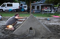Switzerland. Canton Ticino. Tenero. Camping Campofelice. A swiss german man build a sand pyramid on the beach. Sand art is the practice of modelling sand into an artistic form, such as sand sculpture. A sandcastle is a type of sand sculpture resembling a miniature building, often a castle (or a pyramid). A pyramid is a structure whose outer surfaces are triangular and converge to a single point at the top. A campervan (or camper van), sometimes referred to as a camper, or a caravanette, is a self-propelled vehicle that provides both transport and sleeping accommodation. A motorhome (or motor coach is a type of self-propelled recreational vehicle (RV) which offers living accommodation combined with a vehicle engine. Motorhomes are part of the much larger associated group of mobile homes which includes caravans, also known as tourers, and static caravans. A caravan, travel trailer, camper or camper trailer is towed behind a road vehicle to provide a place to sleep which is more comfortable and protected than a tent. It provides the means for people to have their own home on a journey or a vacation. Campers are restricted to designated sites for which fees are payable. 21.07.2018 © 2018 Didier Ruef