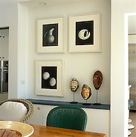 Three black and white photographic prints hang above a display of ethnic masks on top of a built in cupboard in the dining room