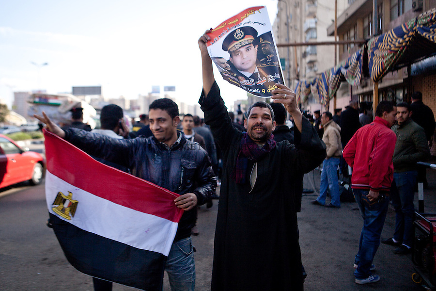 EGYPT, Cairo :An Egyptian man holds a portrait of Egypt's Defence Minister General Abdel Fattah al-Sisi outside a polling station during the vote on a new constitution on January 15, 2014 in Nasr City, Cairo. Egyptians queued to vote on a new constitution today amid high security, in a referendum likely to launch a presidential bid by the army chief who overthrew Islamist president Mohamed Morsi. AFP PHOTO/VIRGINIE NGUYEN HOANG