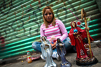 A Mexican devotee shows figurines of Santa Muerte (Saint Death) in her altar outside the shrine in Tepito, a violent neighborhood of Mexico City, Mexico, 1 June 2011. The religious cult of Santa Muerte is a syncretic fusion of Aztec death worship rituals and Catholic beliefs. Born in lower-class neighborhoods of Mexico City, it has always been closely associated with crime. In the past decades, original Santa Muerte's followers (such as prostitutes, pickpockets and street drug traffickers) have merged with thousands of ordinary Mexican Catholics. The Saint Death veneration, offering a spiritual way out of hardship in the modern society, has rapidly expanded. Although the Catholic Church considers the Santa Muerte's followers as devil worshippers, on the first day of every month, crowds of believers in Saint Death fill the streets of Tepito. Holding skeletal figurines of Holy Death clothed in a long robe, they pray for power healing, protection and favors and make petitions to 'La Santísima Muerte', who reputedly can make life-saving miracles.