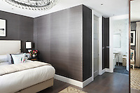 A contemporary bedroom hung with a subtly textured grey wallpaper