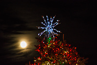 The Christmas star atop the city Christmas tree with a near full moon rising behind,