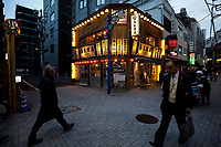 Salarymen walk past a bar hung with lanterns in a street in Kanda, Tokyo, Japan. Monday April 1st 2019