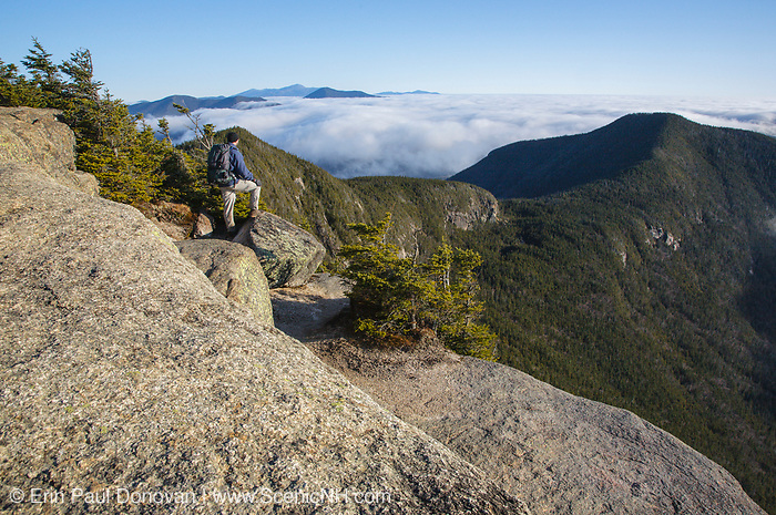 A hiker takes in the view of undercast from the summit of Mount Osceola in the White Mountains, New Hampshire.