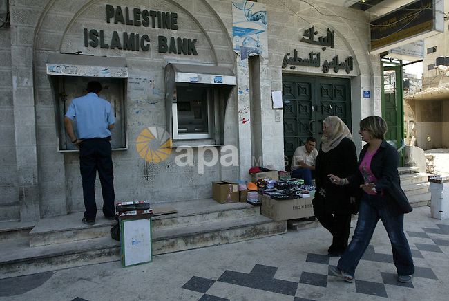 Palestinians walk past the door of the Palestinian Islamic Bank in Gaza City on June 28, 2010 as banks across the Gaza  Strip were closed to protest the seizure of 16,000 dollars (13,000 euros) at gunpoint by Hamas police during a raid a day earlier. Photo by Ashraf Amra
