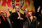 """Kiev, Ukraine.December 26, 2004..Opposition candidate Viktor Yushchenko takes center stage on Maidan Independence Square as thousands of Orange flag waving supporters rally to his side. Election polls show him in a strong lead just hours after the polling stations close. He is joined on stage by his wife Kathy (far left), two children and his political partner Yulia Timoshenko. ..The first round of voting was considered fraudulent when the ruling president Viktor Yahukovich won and the opposition candidate Viktor Yushchenko lost. ..Several hundred thousand Ukrainians took to the streets of Kiev and held daily rallies on Maidan Independence Square. The protests lasted nearly a month before the first vote was declared invalid and a new round of elections held on December 26, 2004. ..The demonstrations would come to be known as the """"Orange Revolution"""" after the color of the opposition party."""