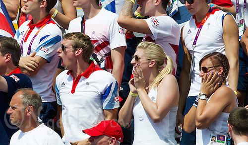 09 AUG 2012 - LONDON, GBR - David Carry (left), the fiance of competitor Keri-Anne Payne, watches the finish of the London 2012 Olympic Games women's 10km Marathon Swimming in Hyde Park, London, Great Britain with  Rebecca Adlington (centre) and Sophie Allen (right) (PHOTO (C) 2012 NIGEL FARROW)