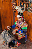 A Miao woman makes pleated skirts by tightly folding fabric on a round log.