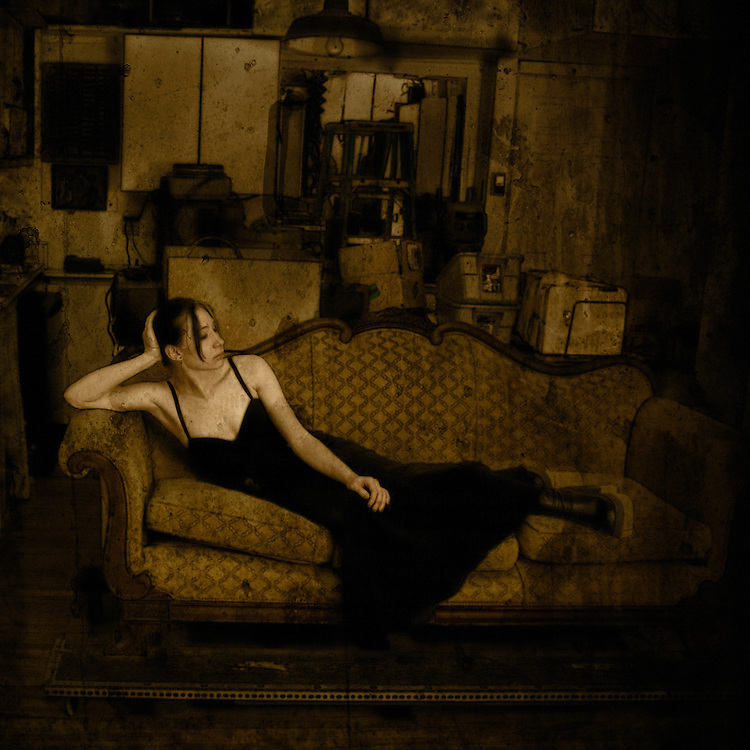 A young woman wearing a long black dress relaxing on an edwardian sofa in a dark room