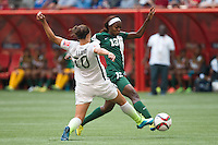 June 16, 2015: Carli LLOYD of the USA and Ngozi OKOBI of Nigeria compete for the ball during a Group D match at the FIFA Women's World Cup Canada 2015 between Nigeria and the USA at BC Place Stadium on 16 June 2015 in Vancouver, Canada. USA won 1-0. Sydney Low/Asteriskimages.com