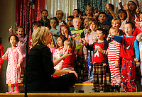 NWA Media/DAVID GOTTSCHALK - 12/16/14 -  Adriane Hapgood, the music teacher at Root Elementary School, leads three kindergarten classes during their performance on stage at Root Elementary School in Fayetteville Tuesday December 16, 2014. The theme of the performance was Holiday Dreams and was performed for the school body in the morning followed by a performance in the evening. Additional photographs available at:  www.nwaonline.com/photos