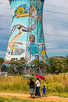 People walking with the painted cooling towers (largest mural in South Africa) of decommissioned Orlando Power Station, now a 300 meter bungee jump, Orlando Towers in background, Soweto, Johannesburg, South Africa.