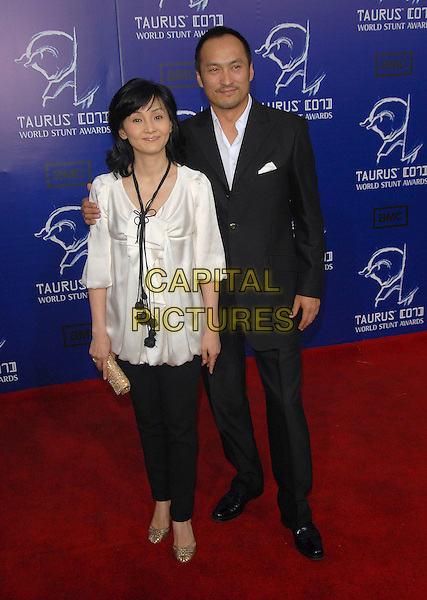 KEN WATANABE & GUEST.The 2007 Taurus Stunt Awards held at Paramount Studios in Hollywood, California, USA..May 20th, 2007.full length black suit white satin top trousers gold clutch purse .CAP/DVS0.©Debbie VanStory/Capital Pictures