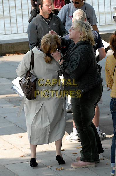 "EMMA THOMPSON .On the set of ""Last Chance Harvey"" refilming scenes near The Royal Festival Hall, Embankment, London, England..May 21st, 2008.film movie full length beige trench coat mac back behind rear eyedrops bending leaning backwards bag purse brown .CAP/IA.©Ian Allis/Capital Pictures."